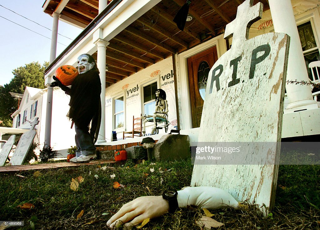 Wearing a maskKyndra Hendrick 6yearsold helps her parents put out Halloween decorations in front of her house October 17 2004 in Owings Maryland...