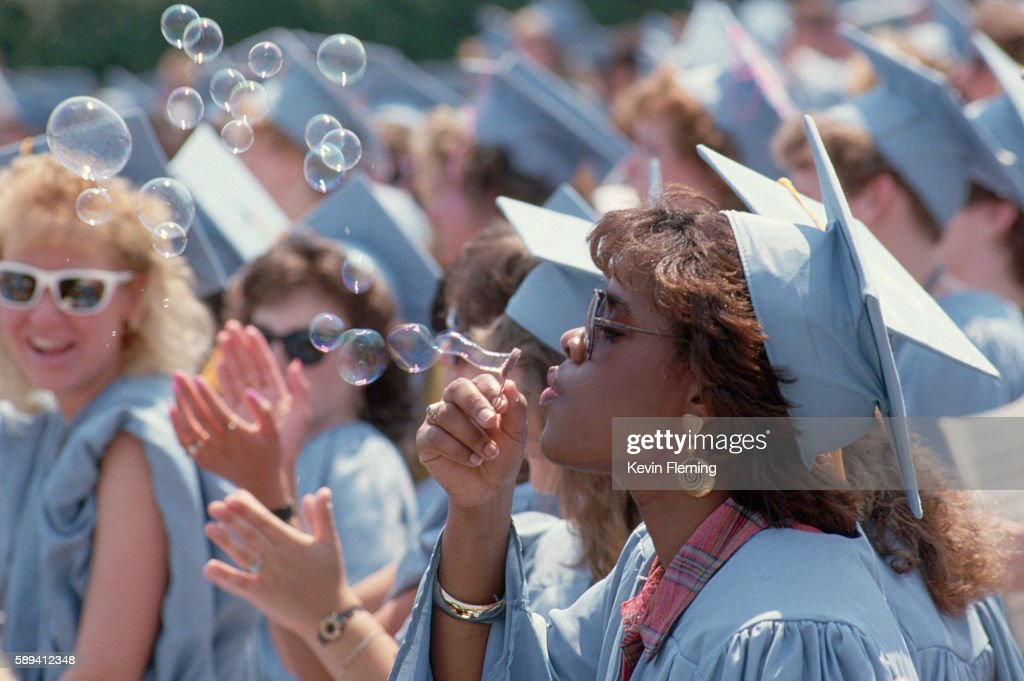 Wearing a pale blue cap and gown a graduate blows soap bubbles during University of Delaware graduation ceremonies at Delaware Stadium Newark Delaware