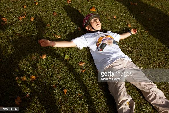 Wearing a safety helmet and tshirt a nine yearold girl cyclist pretends to be asleep having has collapsed on the grass at Peckham Rye Park in South...