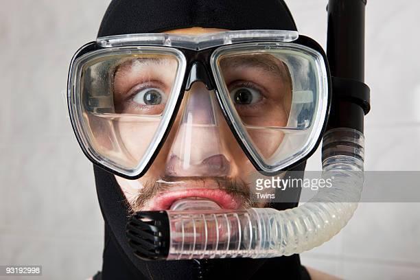 A wearing a scuba mask half full of water