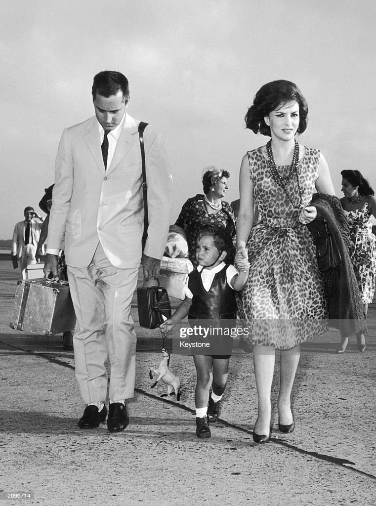 Wearing a sleeveless leopard-print dress and a triple strand of long beads, film star Gina Lollobrigida. She is at Rome airport with her husband Milko Skofic and their son on a visit to Italy from their home in Canada.