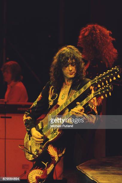 Wearing a suit decorated with oriental dragon motifs English guitarist Jimmy Page performs at Earl's Court playing a Gibson EDS1275 Doubleneck six...