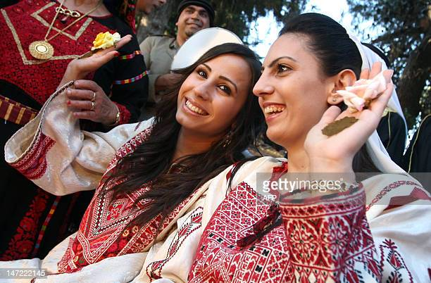 Wearing a traditional cross stitch decorated dress newly wed Nidal whose wedding was last week holds up a flower and henna dye paste in her hand as...