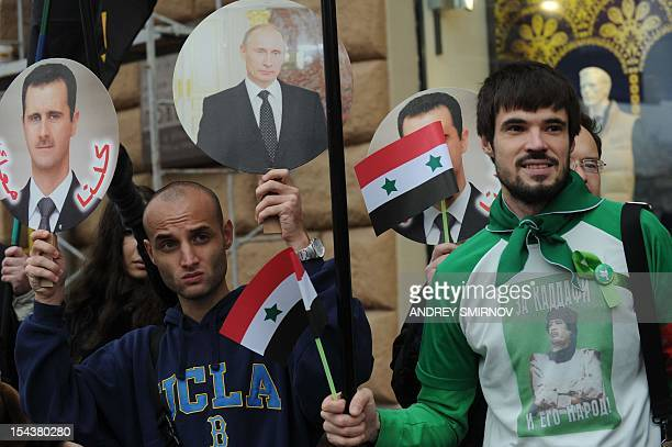 Wearing a Tshirt with an image of late Libyan leader Moamer Kadhafi a demonstrator stands next to his fellow holding portraits of Russia's President...