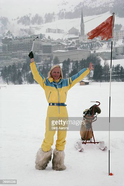 Wearing a yellow skisuit and yeti boots and with a golf trolley on skis Didi Fenton on 'the green' of a snow covered golf course at St Moritz
