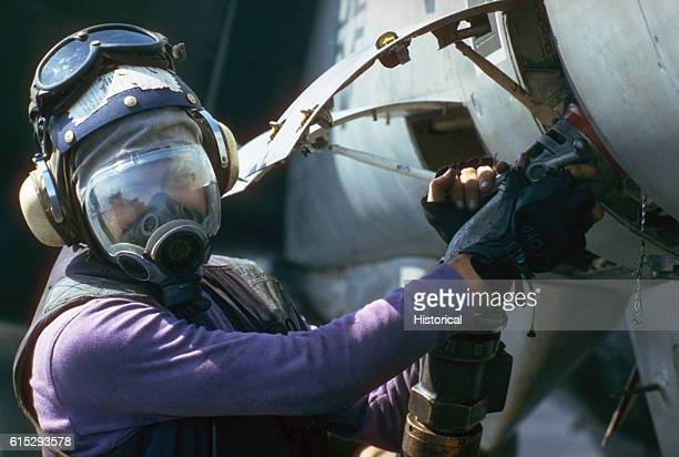 Wearing an MCU2P protective mask as part of a nuclearbiologicalchemical warfare drill an aviation boatswain's mate refuels an F14A Tomcat aircraft on...