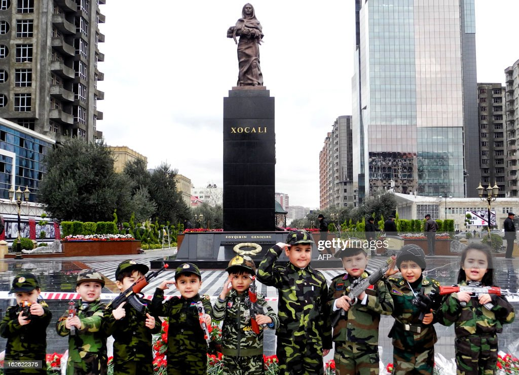 Wearing army-style camouflage costumes little Azerbaijanis take part in a ceremony to mark 21st anniversary of what Azerbaijan refers to as the 'Khojaly Massacre' at a monument to the Khojaly victims in Baku, the capital of Azerbaijan, on February 25, 2013 . Azerbaijani authorities say 613 people died when Armenian troops attacked the village of Khojaly in Karabakh in 1992 during Nagorny-Karabakh conflict in what Baku has described as 'genocide', a term fiercely rejected by Yerevan.