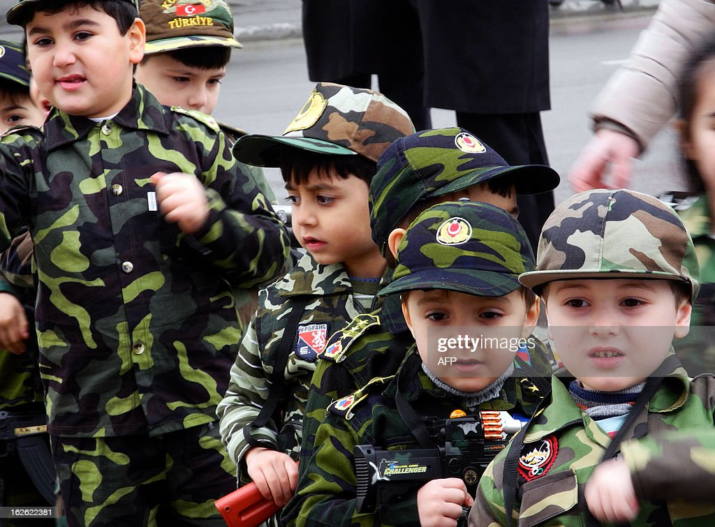 Wearing army-style camouflage costumes little Azerbaijanis take part in a ceremony to mark the 21st anniversary of what Azerbaijan refers to as the 'Khojaly Massacre' at a monument to the Khojaly victims in Baku, the capital of Azerbaijan, on February 25, 2013 . Azerbaijani authorities say 613 people died when Armenian troops attacked the village of Khojaly in Karabakh in 1992 during Nagorny-Karabakh conflict in what Baku has described as 'genocide', a term fiercely rejected by Yerevan. AFP PHOTO/ TOFIK BABAYEV