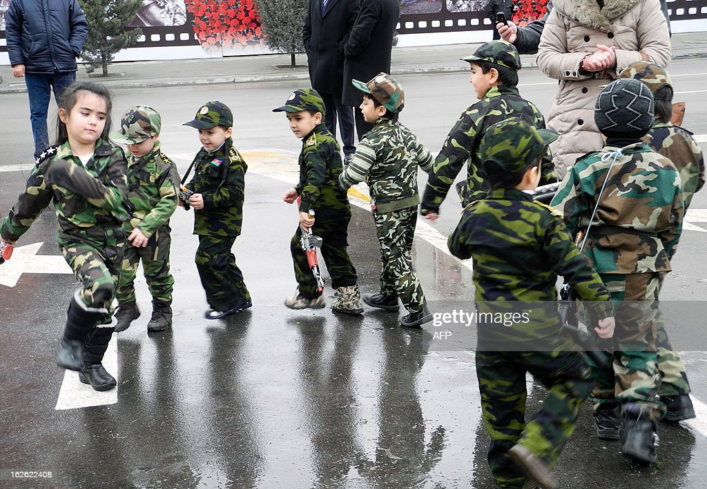 Wearing army-style camouflage costumes little Azerbaijanis take part in a ceremony to mark the 21st anniversary of what Azerbaijan refers to as the 'Khojaly Massacre' at a monument to the Khojaly victims in Baku, the capital of Azerbaijan, on February 25, 2013. Azerbaijani authorities say 613 people died when Armenian troops attacked the village of Khojaly in Karabakh in 1992 during Nagorny-Karabakh conflict in what Baku has described as 'genocide', a term fiercely rejected by Yerevan. AFP PHOTO/ TOFIK BABAYEV