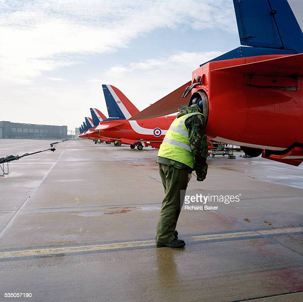 Wearing eardefendersmilitary green camouflage and fluorescent tabard a 'line' engineer from the elite 'Red Arrows' Britain's prestigious Royal Air...