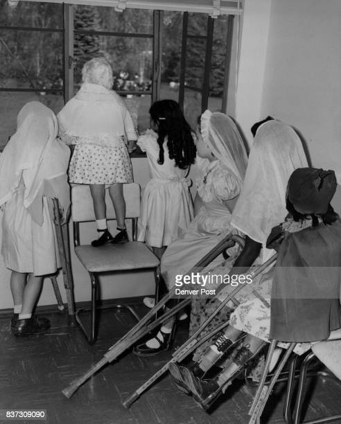 Wearing festive costumes they made themselves for their program these children convalescing at St Anne's home peer out the window during the...