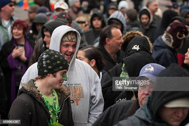 Wearing green paint Darren Austin and his son Tyler wait in line to purchase marijuana at the 3D Denver Discrete Dispensary on January 1 2014 in...