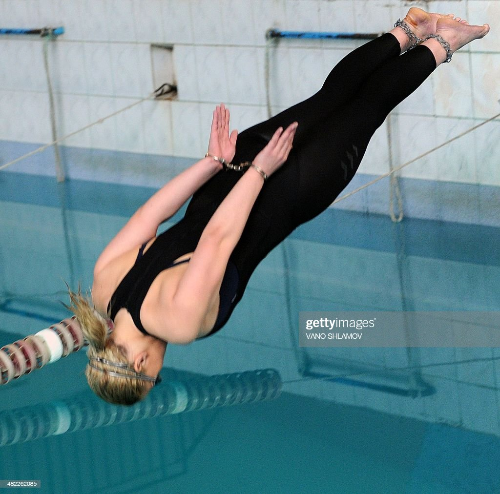 Wearing handcuffs and leg-irons 19-year-old Georgian swimmer Ana Lominadze jumps into a swimming pool during in Tbilisi, on April 3, 2014, during an attempt to set a new Guinness World Record for swimming 25 meters with her hands and feet bound. AFP PHOTO /VANO SHLAMOV