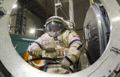 Wearing her spacesuit Russian cosmonaut Elena Serova takes part in a preflight training session with a hatch of the International Space Station at...