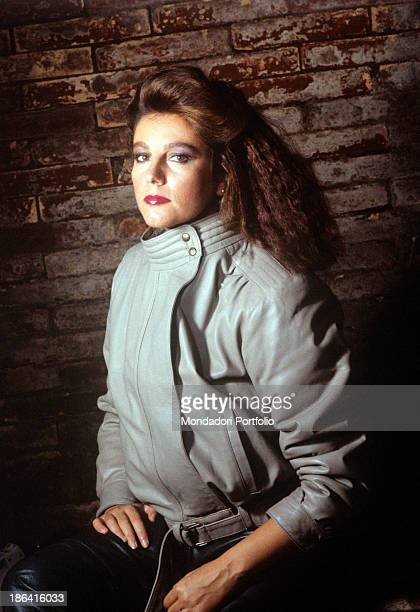 Wearing her wavy hair down the Italian actress Stefania Sandrelli wears leather grey jacket and balck pants on the background a brick wall Italy 1970