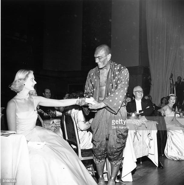 Wearing his costume from 'The King and I' actor Yul Brynner invites CZ Guest to join him in a dance 1953 They are attending a party held in honour of...