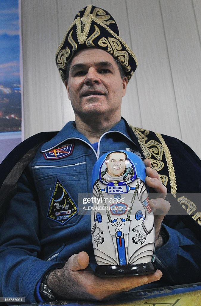 Wearing Kazakh traditional costume US astronaut, Expedition 34 Commander Kevin Ford (2nd R), poses for a photo holding Matryoshka wooden doll with his portrait at the airport of Kostanay, on March 16, 2013, after the landing in northern Kazakhstan. The three astronauts, Kevin Ford, Russian Soyuz Commander Oleg Novitskiy and Russian Flight Engineer Evgeny Tarelkin, returned safely to Earth from the International Space Station early today, aboard a Russian capsule which landed on the freezing Kazakhstan steppe, mission control said.