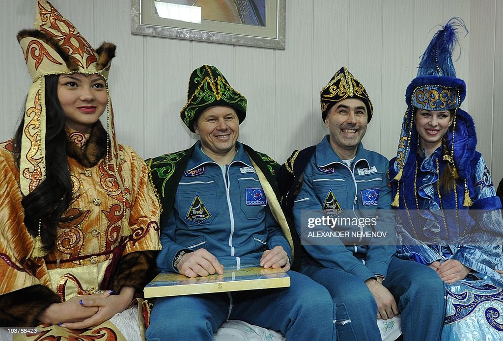Wearing Kazakh traditional costumes Russian Soyuz Commander Oleg Novitskiy (L) and Russian Flight Engineer Evgeny Tarelkin (R) pose for a photo with Kazakh girls at the airport of Kostanay after their landing in northern Kazakhstan, on March 16, 2013. NASA US astronaut Kevin Ford together with Russian cosmonauts Oleg Novitskiy and Evgeny Tarelkin returned safely to Earth from the International Space Station early today, aboard a Russian capsule which landed on the freezing Kazakhstan steppe, mission control said.The landing had been delayed by a day due to poor weather conditions, but rescue helicopters still had to contend with thick ground fog which descended on the landing area and drastically reduced visibility.