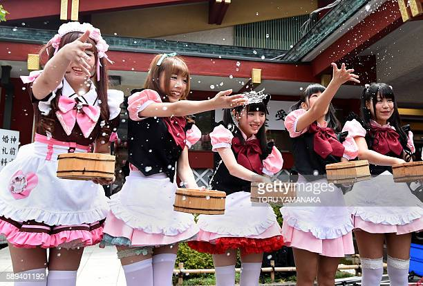 Wearing maid and special characters costumes girls who work in Akihabara geek culture district splash water at Kanda Shrine to cool the precinct in...