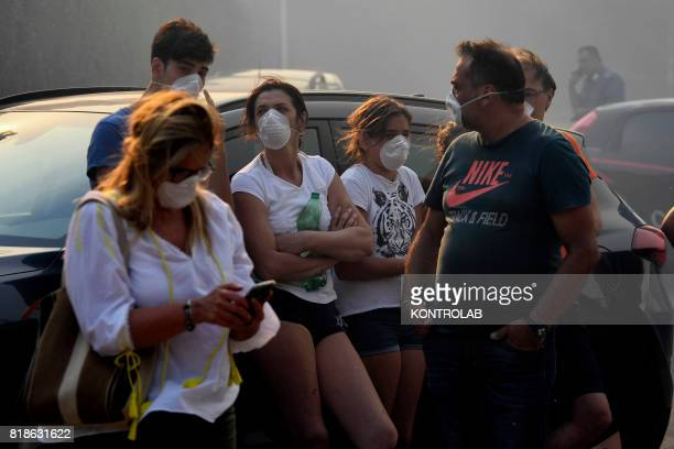 Wearing masks to protect them from the smoke people rest by the side of the road during a vast fire that threatened inhabited areas between Naples...