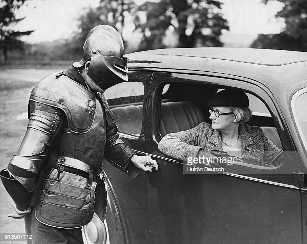 Wearing medieval plate armor Mr H Maskell opens the car door of a visitor to Tudor House in Maidstone Kent England October 30 1937
