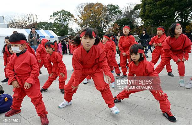 Wearing ninja costumes children stretch before their dance performance during the IgaUeno Ninja Festival is on display at the entrance of the event...