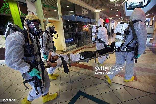 Wearing protective suits Israeli police evacuate the 'victim' of a chemical warfare terror attack in a shopping mall during a training exercise on...