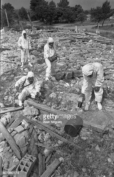 Wearing protective suits members of the Cellule Mobile d'Intervention Radiologique unit of French firefighters test the ground for radioactivity CMIR...