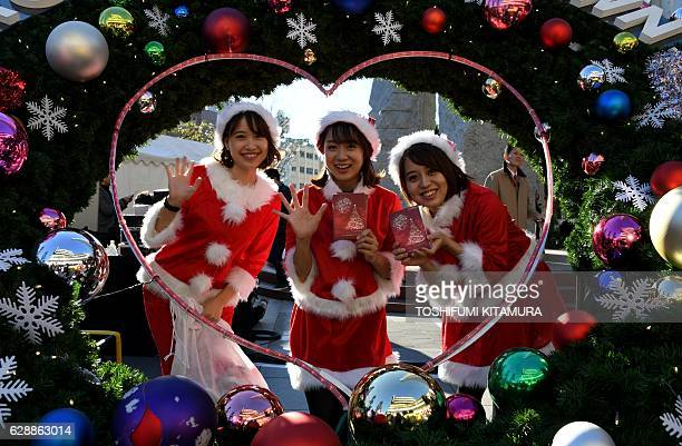 Wearing Santa Claus costumes employees of a toy maker pose in an event underneath the landmark Tokyo Sky Tree in Tokyo on December 10 2016 The Japan...