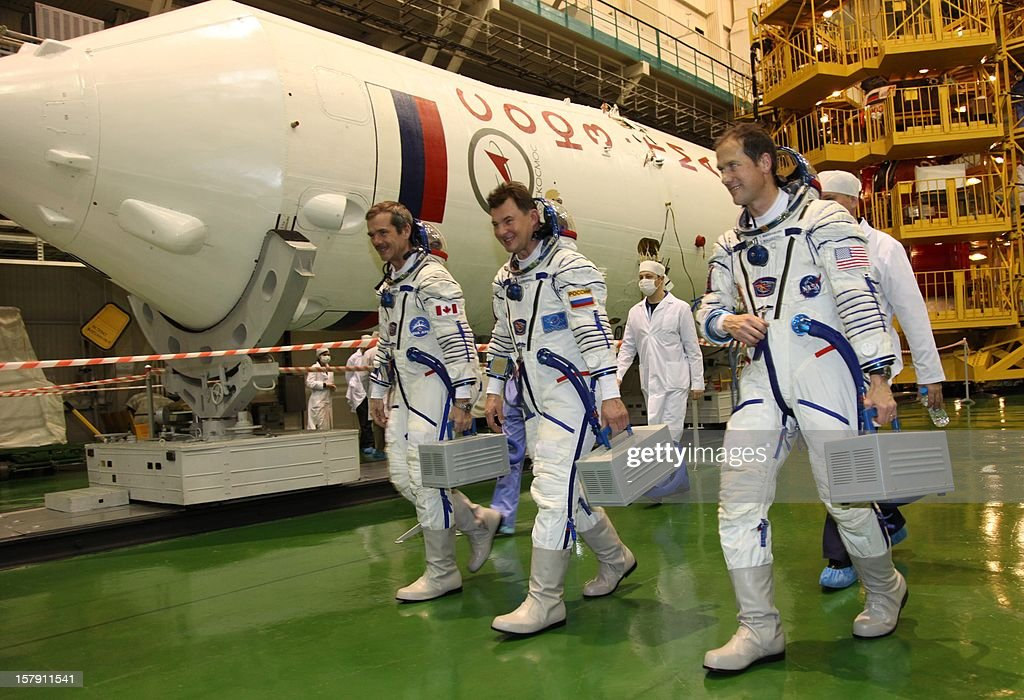 Wearing their space suits crew members of the next expedition to the International Space Station (L-R), Canadian astronaut Chris Hadfield, Russian cosmonaut Roman Romanenko and US astronaut Tom Marshburn, take part in the preflight preparation at the Russian leased Kazakhstan's Baikonur cosmodrome on December 7, 2012. Hadfield, Romanenko and Marshburn will join in December the remaining ISS crew, Russians Oleg Novitskiy and Evgeny Tarelkin, and Kevin Ford of the United States, who arrived there last month. AFP PHOTO / STR