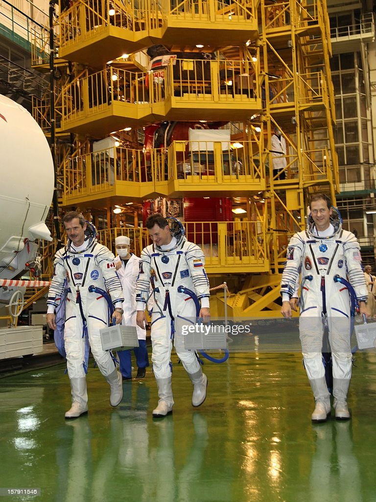 Wearing their space suits crew members of the next expedition to the International Space Station Canadian astronaut Chris Hadfield Russian cosmonaut...