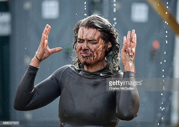 A weary competitor uses an outdoor shower after taking part in the Mud Madness race at Foymore Lodge on September 13 2015 in Portadown Northern...
