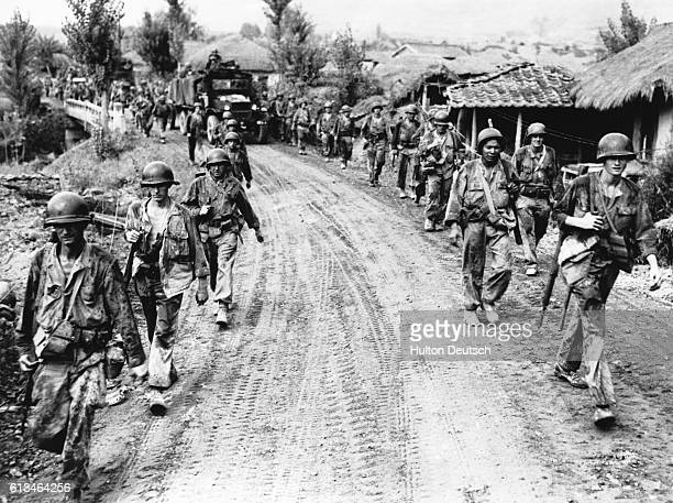 Weary Mud Bespattered United States Troops File Through Yongsan The scene as weary mud bespattered American troops file along either side of the road...
