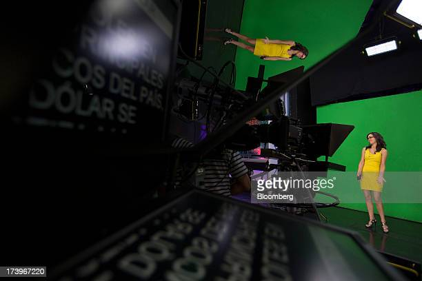 A weather presenter for Grupo Televisa SAB's FOROtv news channel stands in front of a green screen as she prepares for a broadcast at the Televisa...