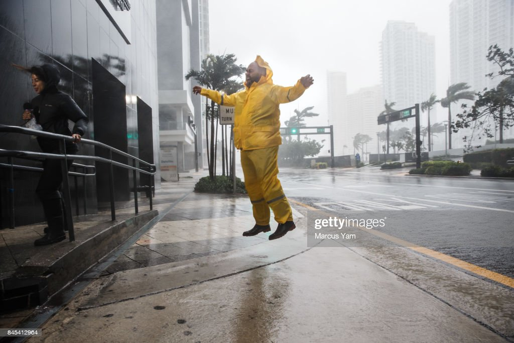 Weather reporters jump and cling on to illustrate the force of the winds caused by Hurricane Irma as it arrives in Miami, Fla., on Sept. 10, 2017.