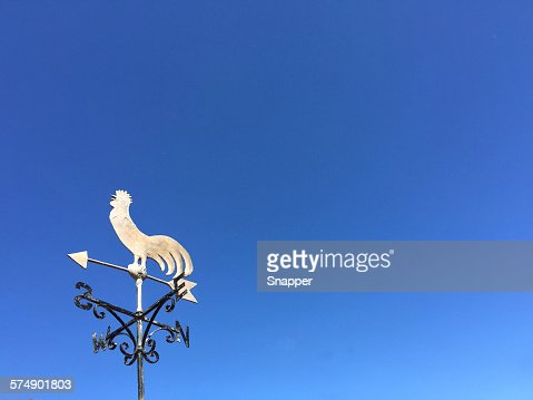 Weather vane against a clear blue sky