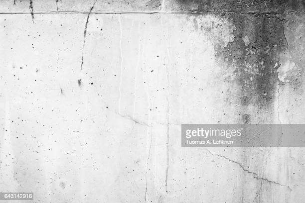 Weathered and moldy concrete wall with cracks in black&white.