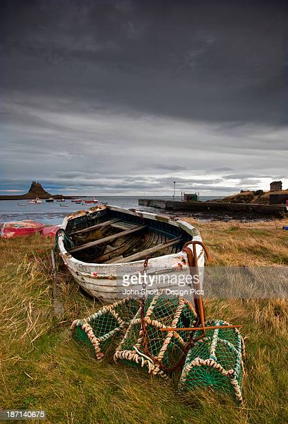 A Weathered Boat And Fishing Equipment Sitting On The Shore With Lindisfarne Castle In The Distance