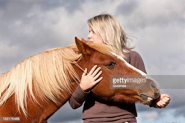 Weathering the storm together-girl and horse in close up.