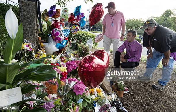 TV weatherman Leo Hirshbrunner views the makeshift memorial with members of the crew at the gate of WDBJ's television studios August 27 in Roanoke...