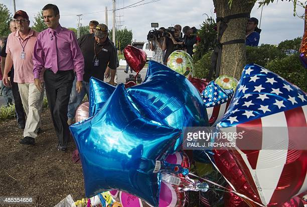 TV weatherman Leo Hirshbrunner walks by the makeshift memorial with members of the crew at the gate of WDBJ's television studios August 27 in Roanoke...