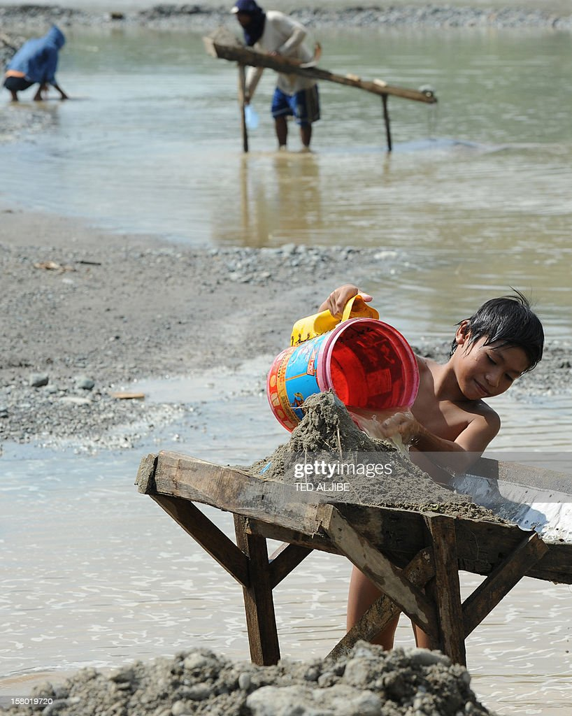 Weather-Philippines-typhoon-mining-environment,FOCUS by Mynardo Macaraig A boy helps his family sift through sand as he pans for gold dust at a river in the town of Mawab in Compostela Valley province on December 9, 2012 near some of the worst affected areas damaged by Typhoon Bopha. Unchecked illegal gold mining and decades of indiscriminate logging contributed to the high death toll in the Philippines' worst natural disaster this year, officials and experts say.
