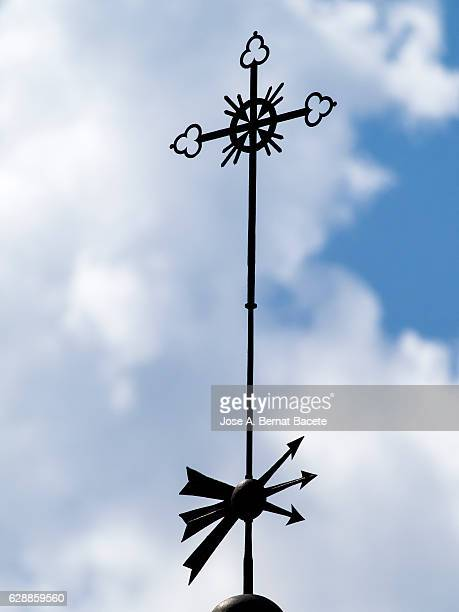 Weathervane on the tower of a church with a cross and a group of arrows