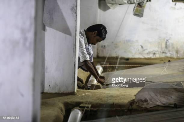 A weaver arranges silk threads on a handloom to make a silk saree in a workshop at night in Varanasi Uttar Pradesh India on Friday Oct 27 2017 In...