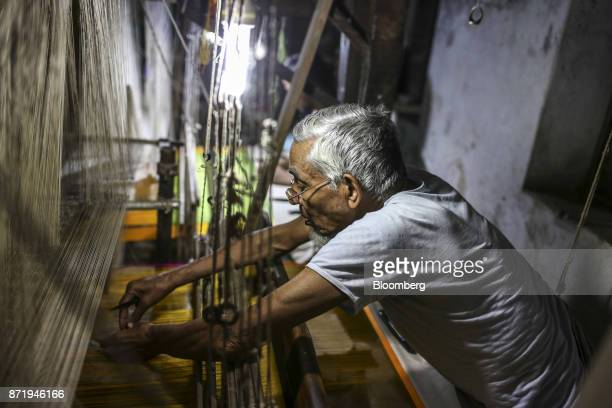 A weaver arranges the silk threads on a handloom while making a silk saree in a workshop at night in Varanasi Uttar Pradesh India on Saturday Oct 28...