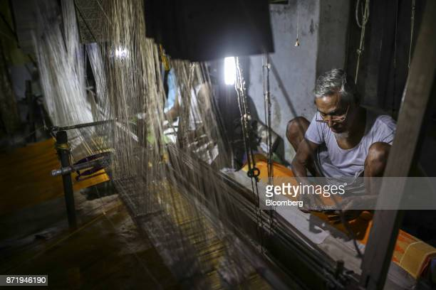 A weaver looks at a design template while sitting at a handloom making a silk saree in a workshop at night in Varanasi Uttar Pradesh India on...