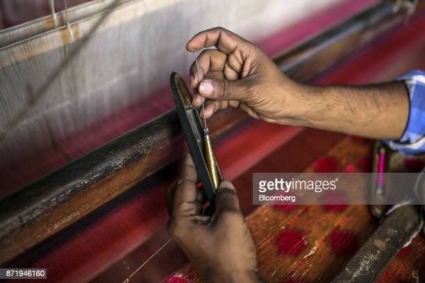 A weaver puts a spool of gold silk thread on to a shuttle at a workshop in Varanasi Uttar Pradesh India on Friday Oct 27 2017 In Varanasi where the...