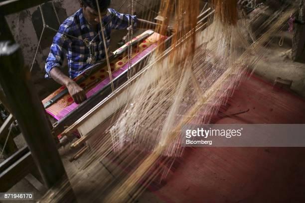 A weaver uses a handloom to make a silk saree at a workshop in Varanasi Uttar Pradesh India on Friday Oct 27 2017 In Varanasi where the manufacture...