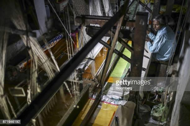 A weaver uses a handloom to make a silk saree in a workshop at night in Varanasi Uttar Pradesh India on Saturday Oct 28 2017 In Varanasi where the...