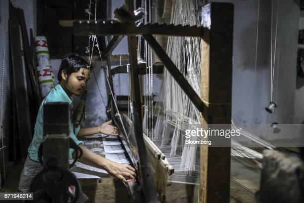 A weaver uses a handloom to make a silk saree in a workshop at night in Varanasi Uttar Pradesh India on Friday Oct 27 2017 In Varanasi where the...